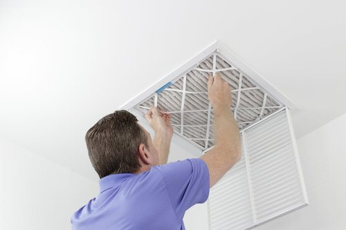 Professional removing an air filter from a ceiling air duct