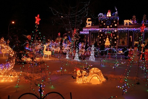Magical snowed front-yard full of colorful Christmas lights