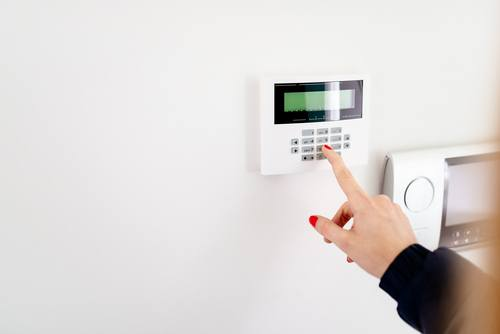 Woman setting burglar alarm with her home security system