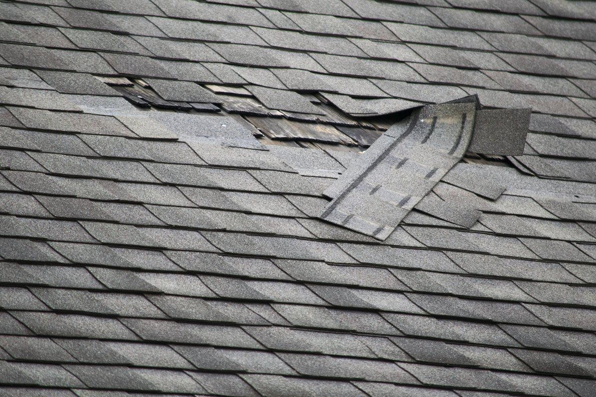 Roof with missing and damaged shingles