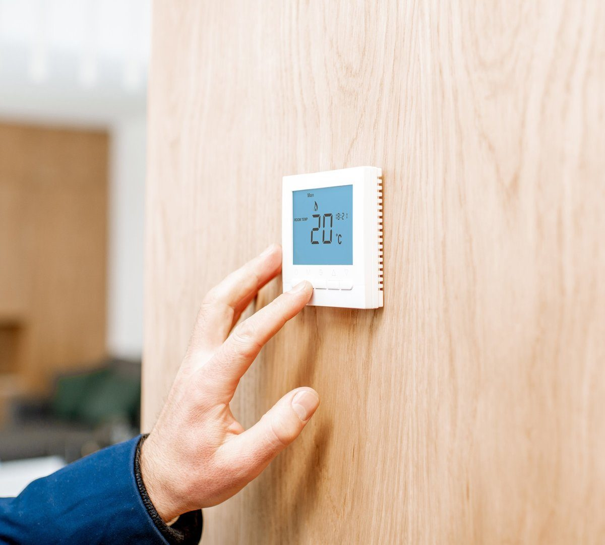Manual thermostat installed on a wooden wall