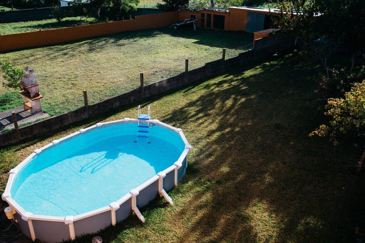 Une piscine hors sol ovale sur l'herbe dans l'arrière-cour sur une journée d'été ensoleillée