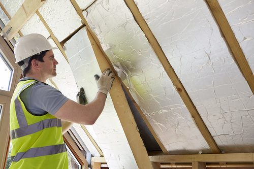 Professional putting insulation material on the walls of an attic