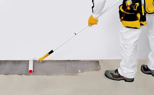 Professional waterproofing the basement floor with waterproof paint