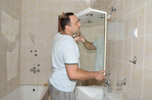 Handyman installing a bathroom mirror