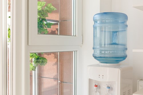 Bottled water in a water dispenser next to a window