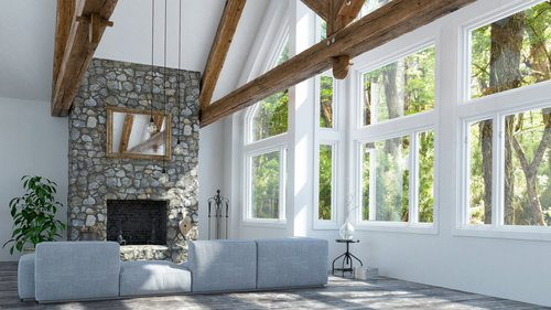 Stone fireplace built in a big luminous living room in front of a gray couch