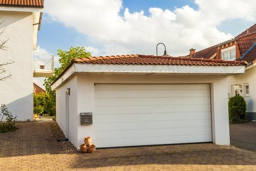 Detached white garage with orange tile roof