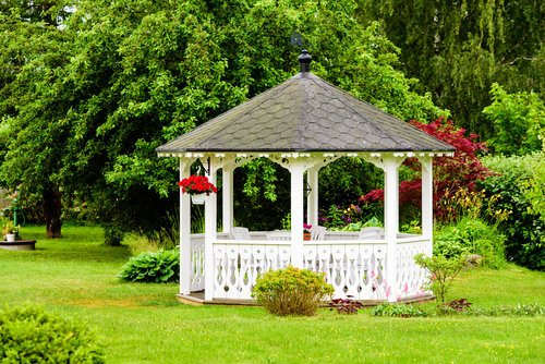 Octagonal white gazebo in a beautifully landscaped backyard
