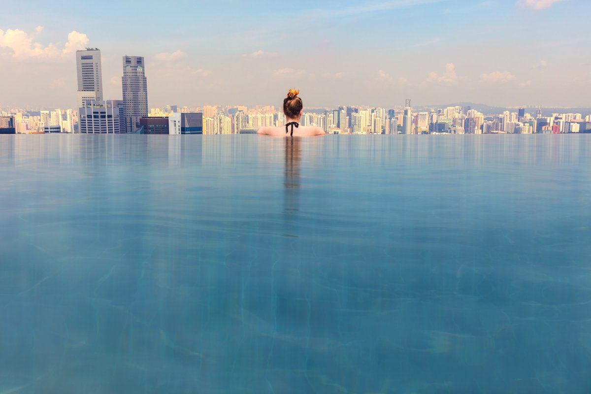 Woman bathing in an infinity pool located on a rooftop