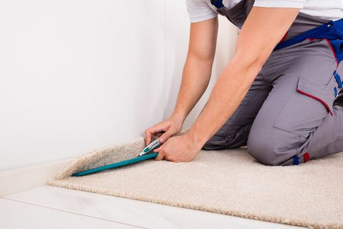 Professional installing light-colored carpet