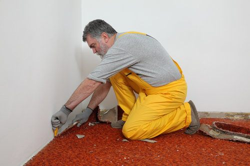 Professional removing carpet in a room