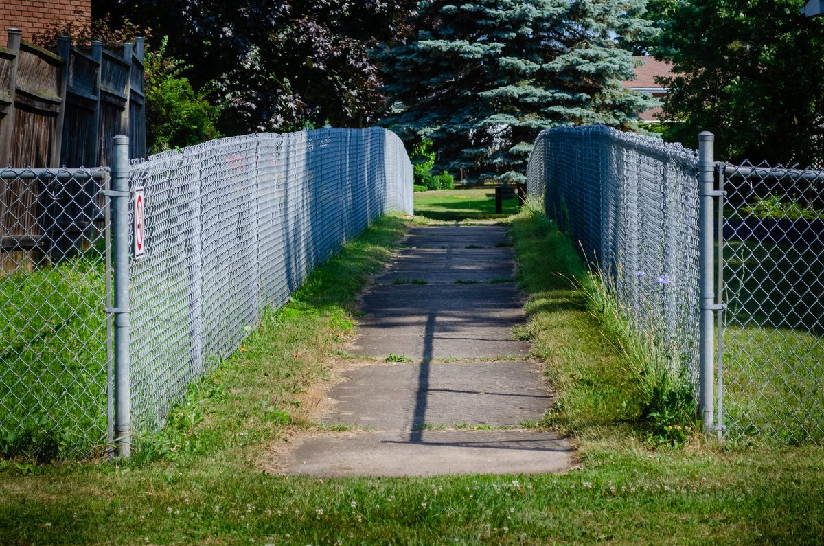Entrance of chain link fenced concrete sidewalk pathway in a residential neighborhood