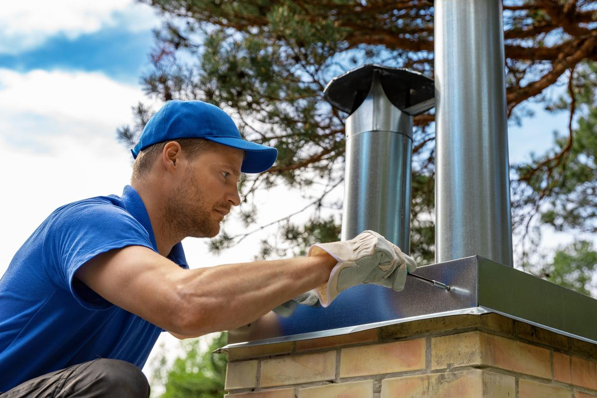 Professional on the roof installing chimney cap on a brick chimney