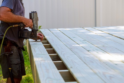 Contractor using a nail gun to repair a deck