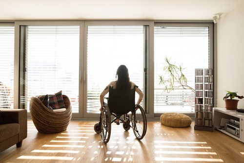 Woman with a disability looking through a window in a remodeled living room