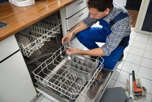 Male technician repairing dishwasher in kitchen