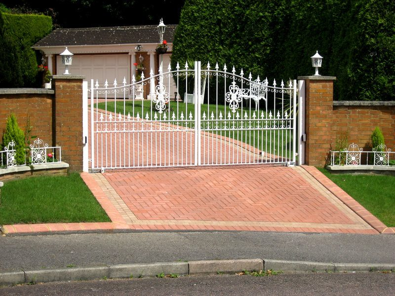 White driveway gate installed on a red brick paver driveway