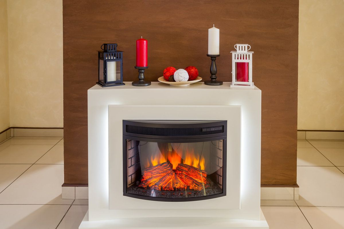 White electric fireplace with candles on top