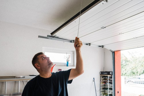 Electrician installing a chain-driven garage door opener