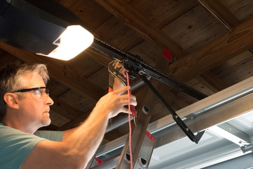 Professional repairing an automatic garage door