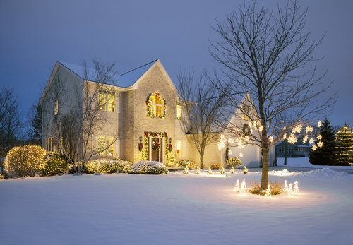 House and trees surrounded by snow and decorated with holiday lights