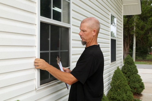 Real Estate Home Appraiser Examining Edge of Window