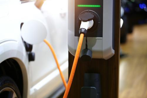 White electric car charging at a charging station
