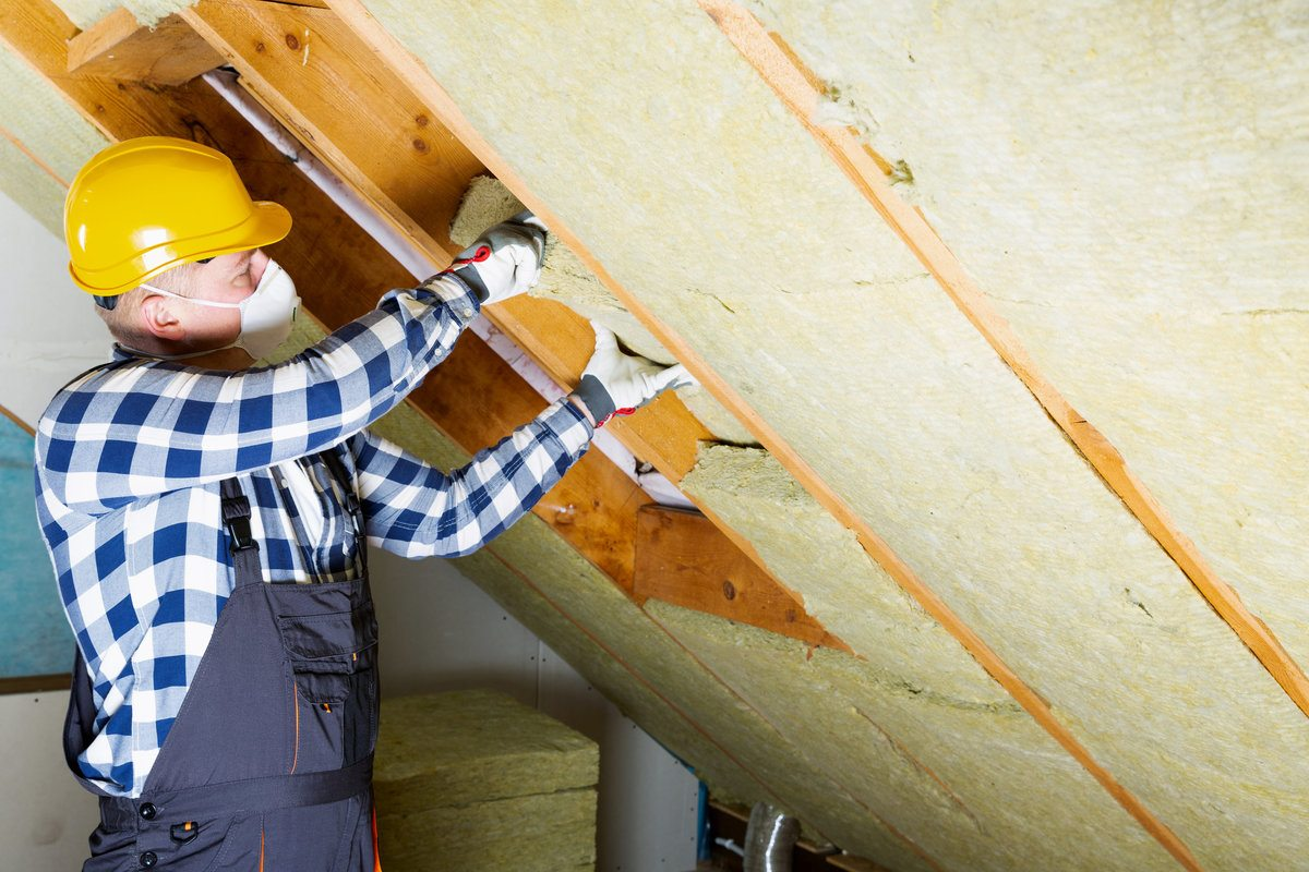 Professional installing thermal roof insulation in the attic