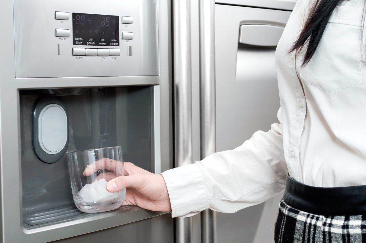Woman putting her glass under the ice maker to get some ice cubes.