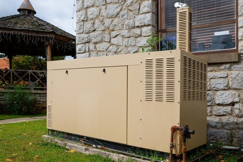 Backup generator installed on the backyard close to the house building