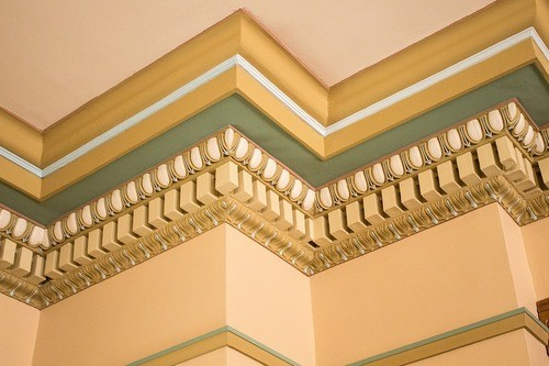 Classical plaster crown molding painted in yellow and green decorated with an intricate design