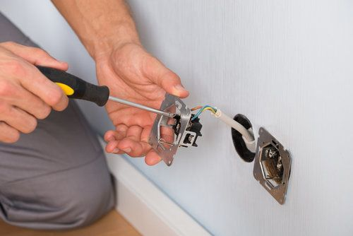 Electrician using a screwdriver to attach the power cord to the wall outlet