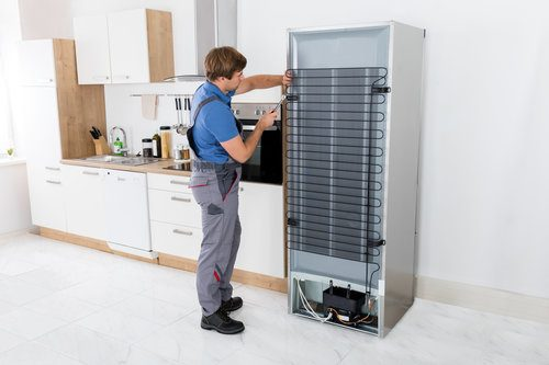 Man installing a stainless steel refrigerator in a kitchen