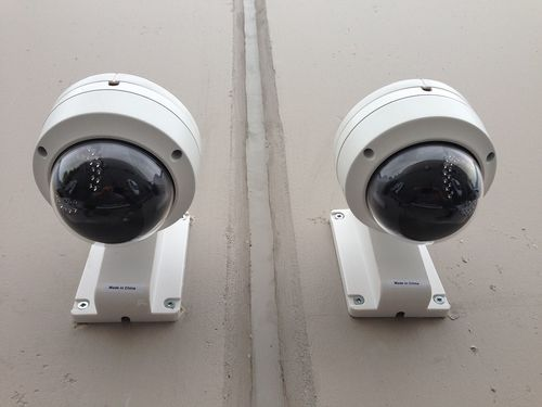 Two outdoor surveillance cameras installed in the façade of a house
