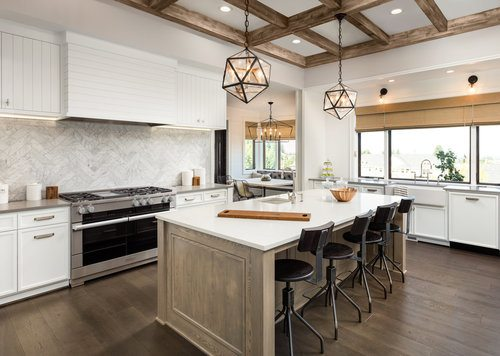 Cooking/dining kitchen island with some black chairs and pendant light fixtures