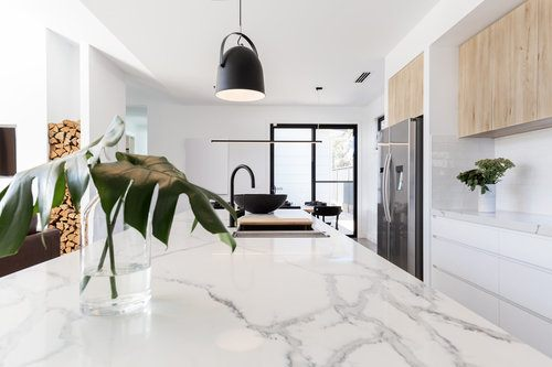 Marble island closeup with black hanging pendant in a modern remodelled kitchen
