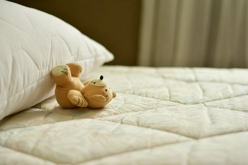 Close-up of a mattress with a teddy bear