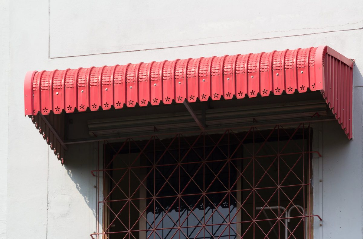 Red metal awning installed on top of a window
