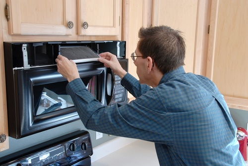 Technician repairing a microwave