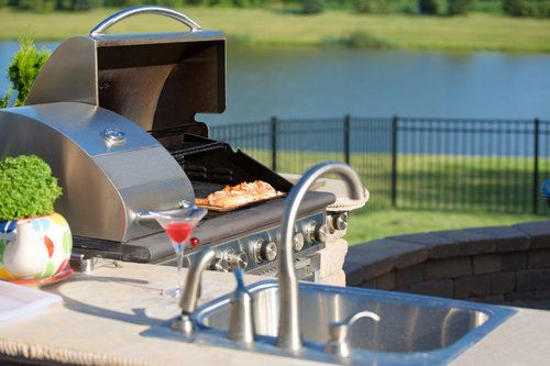 Beautiful outdoor kitchen with a grill and a top-mount sink