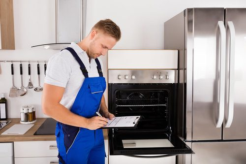 Professional assessing the problems of an oven before repairing it