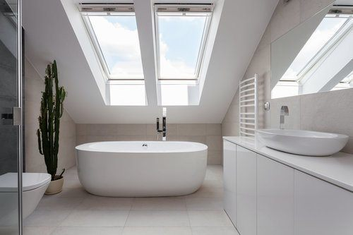 Bathroom painted in white, with a skylight, freestanding bathtub in the back, a toilet on the left, and a sink with countertop and cabinets in the right
