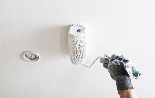 Painter painting a ceiling in white
