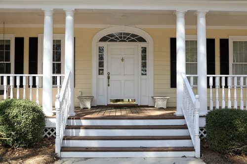 House exterior with covered porch and white exterior door