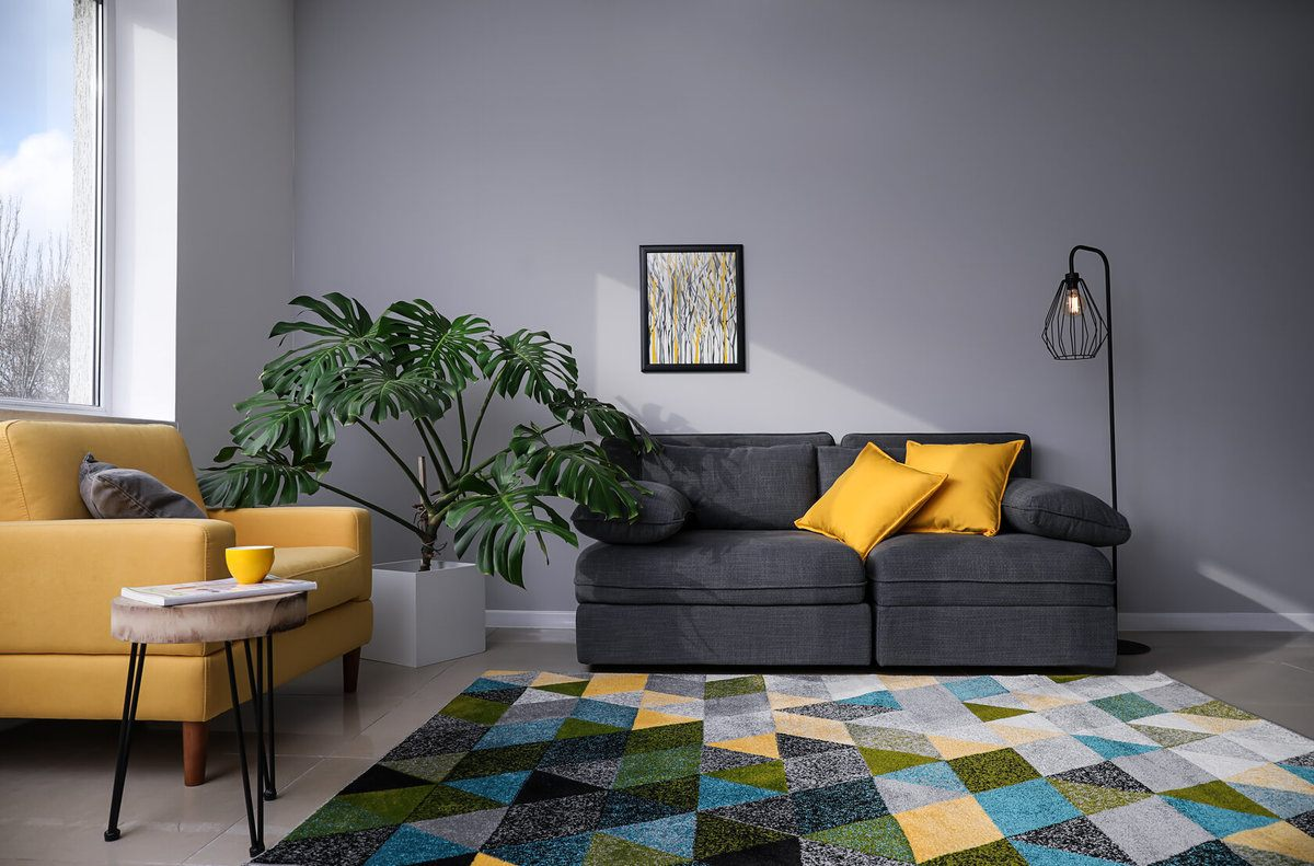 Stylish Living Room With Grey Walls and Couch, Yellow Cushions and a Rug