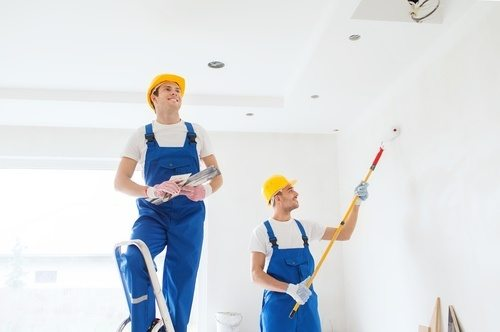 Two painters painting a room with white paint