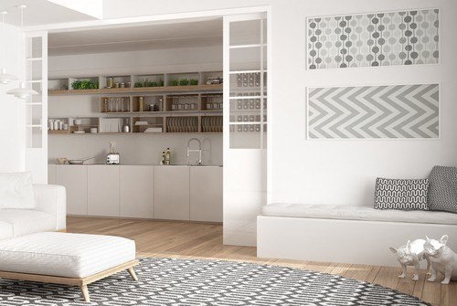 White wooden pocket door installed between a kitchen and a living room