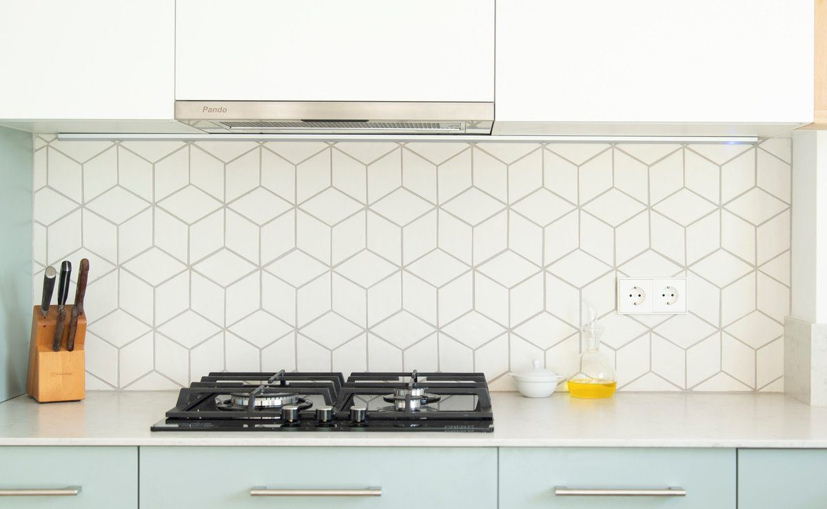 Porcelain tile backsplash in a kitchen with light-blue cabinets and a gas stove