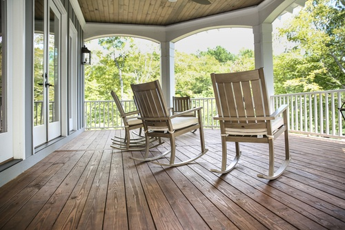 Porch with some wood rocking chairs in a house surrounded by vegetation